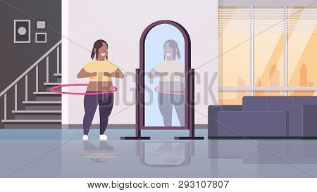 Overweight Woman Doing Gymnastic Rotating Workout With Hula Hoop Looking At Reflection In Mirror Afr