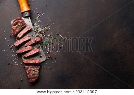 Top blade or denver grilled steak over meat butcher knife. Top view with copy space