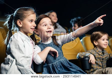 Excited Kid Pointing With Finger While Watching Movie In Cinema Together With Multicultural Friends