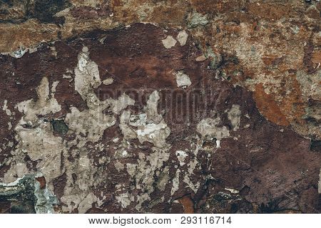 Dark Brown Dirty Flaky Shabby Stucco On The Wall. Abstract Cracked Wall Texture. Old Vintage Stuccoi