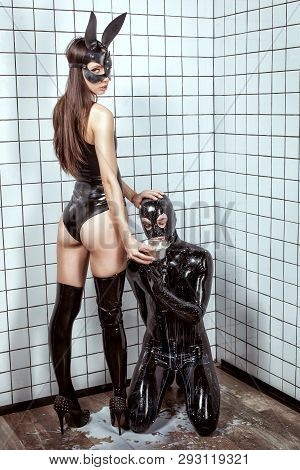Woman Forces A Man To Eat From A Bowl. The Man Is Wearing A Latex Suit. Bdsm Style And Humiliation.