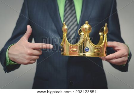 Businessman is showing on a crown in his hand. Award ceremony of the Winner. Time to rule concept. Power of authority. Crown for new king. poster
