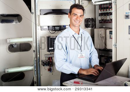 portrait of professional industrial technician in front of machinery