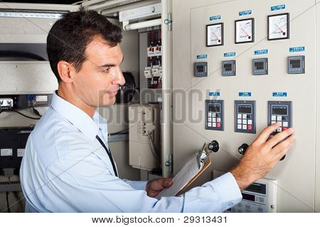 professional industrial engineer adjusting modern machine settings