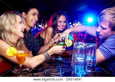 Image of happy girl looking at her glass while young man pouring cocktail into it with friends near by