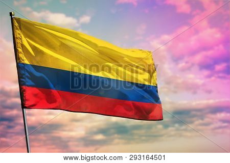Fluttering Colombia Flag On Colorful Cloudy Sky Background. Colombia Prospering Concept.