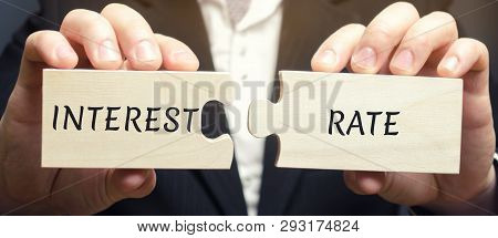 A Man Collects Wooden Puzzles With The Word Interest Rate. The Amount Of Money In The Form Of Intere