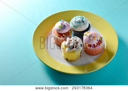 Delicious and tempting mini cup cakes with beautiful icing, served in a dessert plate. Colorful small cup cakes. poster
