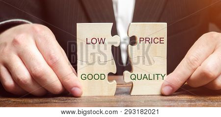 A Businessman Collects Wooden Puzzles With The Words Low Price - Good Quality. The Concept Of Profit