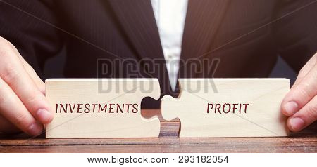 Businessman Collects Puzzles With The Words Investments And Profit. Return On Investment And Investe