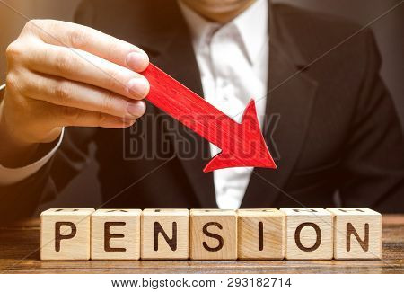 A Man Holds An Arrow Down Over Wooden Blocks With The Word Pension. Fall / Reduction Pension Payment
