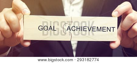 Man collects puzzles with the words Goal achievement. The solution of the problem. Business tools for doing business. Purposefulness and self-reliance, support of a businessman. Motivation, training poster