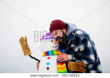 Angry Man Biting Off Snowman`s Nose On Warm Winter Day. Guy Bites Off Nose Snowman. Bearded Man Tryi