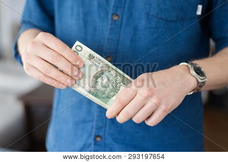 A Rich Young Man In A Casual Blue Shirt Holding A Lot Of Polish Money