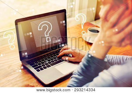 Question Marks With Man Using A Laptop Computer