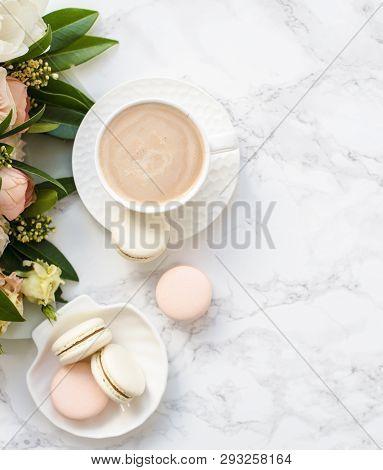 Elegant Sweet Dessert Macarons, Cup Of Coffee And Pastel Colored Beige Flowers Bouquet On White Marb