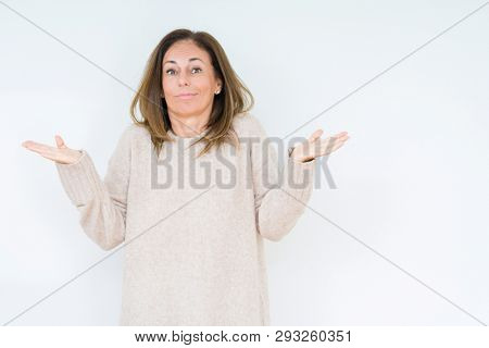 Beautiful middle age woman over isolated background clueless and confused expression with arms and hands raised. Doubt concept.