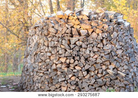 Woodpile. Firewood Stacked In A Woodpile. Large Stock Of Firewood.