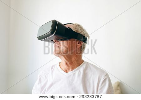 Front view of senior Caucasian male patient using virtual reality headset at retirement home