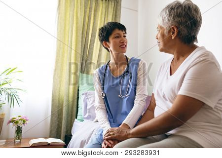 Low angle view of beautiful Asian female doctor interacting with senior African-american female patient at retirement home. They are sitting on bed.