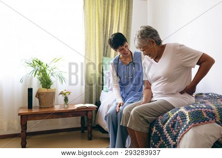 Side view of Asian female doctor and senior female patient interacting with each other at retirement home. Senior woman touching her back, she is in pain.