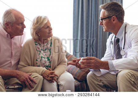 Front view of confident Caucasian male doctor prescription medicine to senior Caucasian couple at retirement home