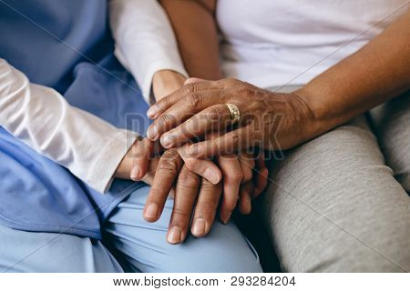 Mid section of Asian female doctor holding hand of senior African-american patient at retirement home