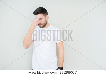 Young handsome man wearing casual white t-shirt over isolated background tired rubbing nose and eyes feeling fatigue and headache. Stress and frustration concept.