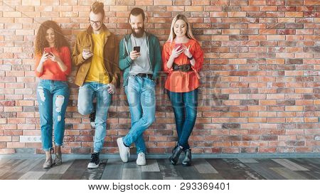 Millennials Social Media Addicted Generation. Young People In Colorful Outfits Leaned Against Brick