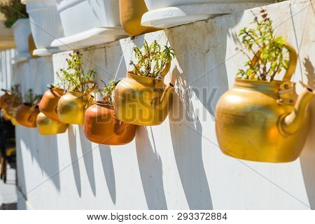 Old rustic copper kettles with plants hanging on white wall. Souq Waqif market, Doha, Qatar poster