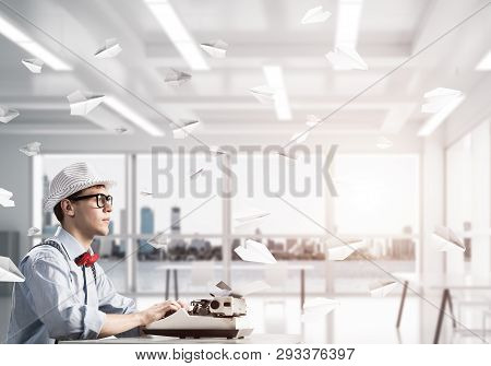 Young Man Writer In Hat And Eyeglasses Using Typing Machine While Sitting At The Table Indoors Among