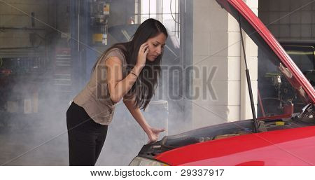 Woman with car troubles talking on cell phone