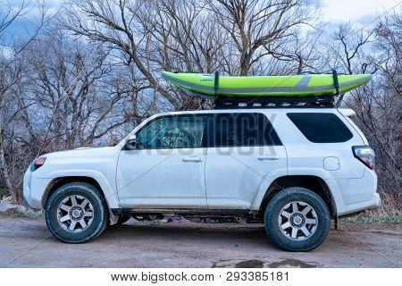 Fort Collins, CO, USA - April 1,  2019 : Toyota 4 Runner SUV (2016 Trail Edition) with a whitewater inflatable kayak (Aire Force) at dusk after paddling on the Poudre River, early spring scenery.