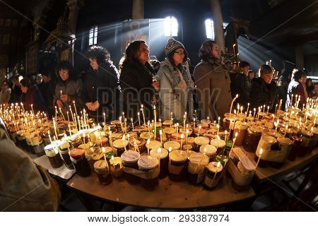 Blagoevgrad, Bulgaria - February 10, 2019: Worshippers Light Candles On Jars With Honey During A Rel