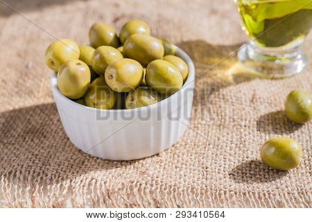 Fresh Marinated Green Olives In White Ceramic Bowl And Sauceboat Of Premium Virgin Olive Oil  On  Bu