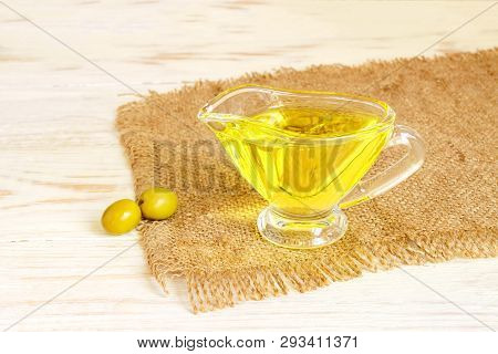 Glass Sauceboat With Extra Virgin Olive Oil And Fresh Green Olives On Burlap Cloth On Wooden Table.