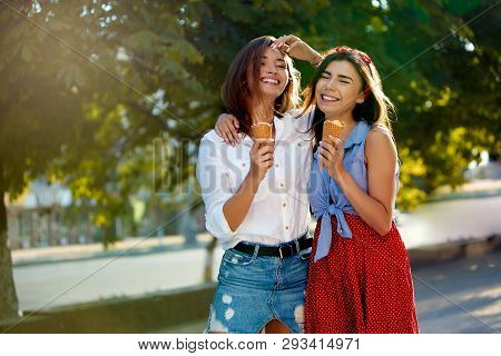 Two Young Female Friends Having Fun And Eating Ice Cream. Cheerful Caucasian Women Eating Icecream O