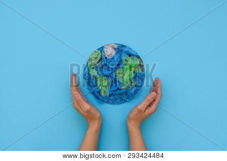 Hands Holding Planet Earth Made From Plastic Disposable Packages On Blue Background. Save The World,