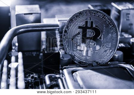 Silver bitcoin among the electronic computer components. Business concept of digital cryptocurrency. Blockchain technology, bitcoin mining concept