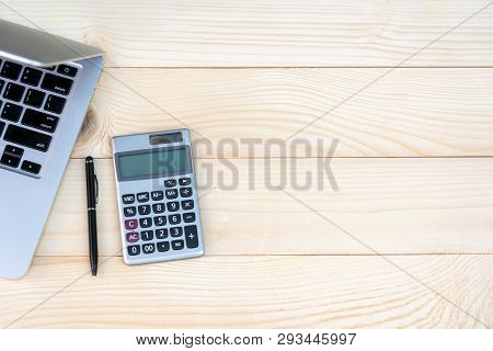 Flat Lay, Top View Office Table Desk. Workspace With Calculator, Black Pen , Laptop On The Pine Wood