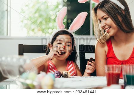 Happy Easter! A Mother And Her Daughter Painting Easter Eggs. Happy Family Preparing For Easter. Cut