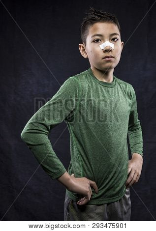 Tough Young Athletic Boy. A Close Up Portraiture Of A Confident Athletic Boy Who Has Tape On His Nos