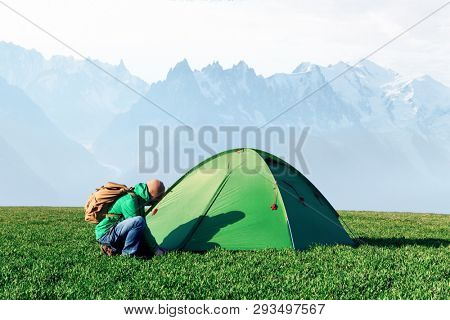 Tourist pitch a tent in summer mountains. Amazing green highland. Landscape photography
