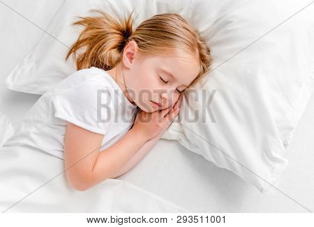 cute little girl with toy sleeping in white bed