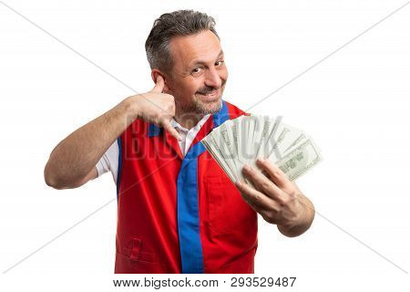 Trustworthy hypermarket or supermarket male employee making call us gesture with fingers near ear and holding money bills isolated on white poster