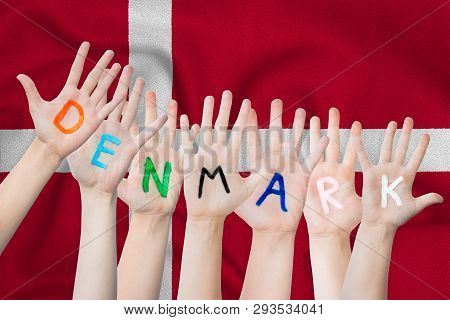 Denmark Inscription On The Children's Hands Against The Background Of A Waving Flag Of The Denmark