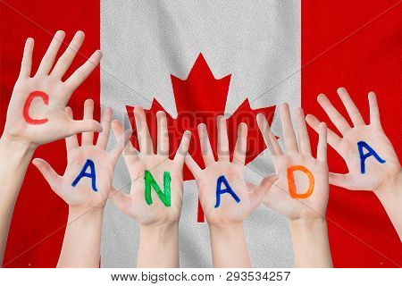 Canada Inscription On The Children's Hands Against The Background Of A Waving Flag Of The Canada