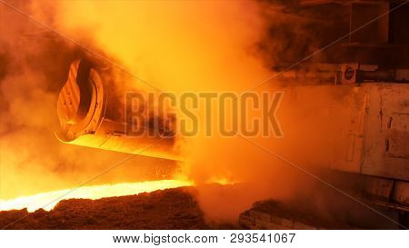 Hot steel production at the steel plant, metallurgy concept. Stock footage. Hot shop with flowing molten steel in the chute. poster