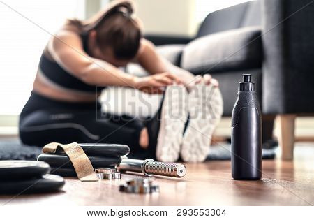 Woman Stretching Muscles Before Gym Workout And Weight Training In Home Living Room. Female Fitness
