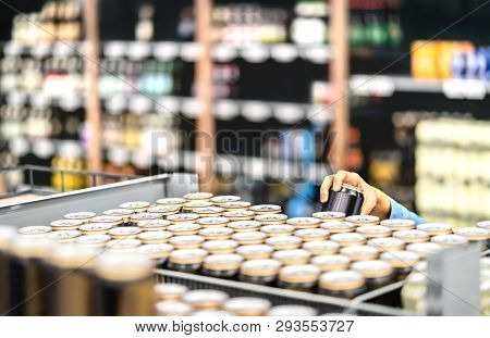 Retail Worker Filling Shelf With Drinks In Grocery Store Or Customer Taking Can Of Beer Or Soda. Sta